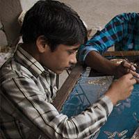 Qayum (12) maakt lange dagen achter de borduurtafel. Samen met zijn moeder Rizwhana, broer Wasim (19 en zus Roma (16) borduurt hij applicaties voor kleding. <a href=